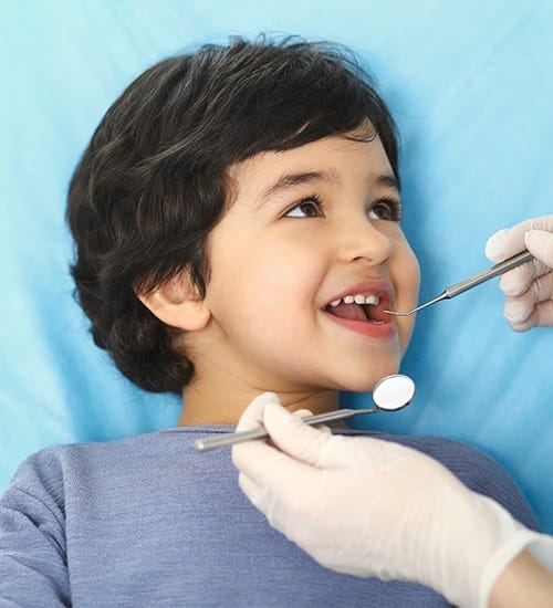 Young child receiving dental exam at first visit