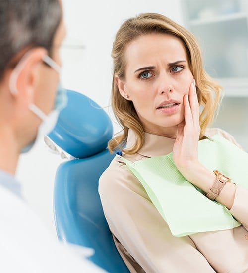 Woman holding cheek during dental crown consultation