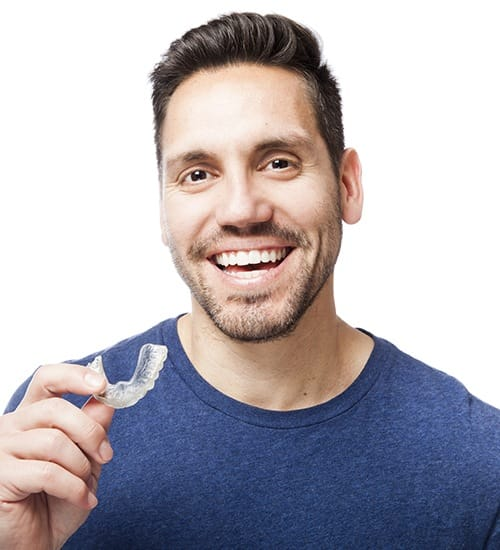 Smiling man holding an orthodontic clear aligner tray