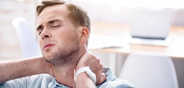 Man in need of T M J therapy holding neck in pain