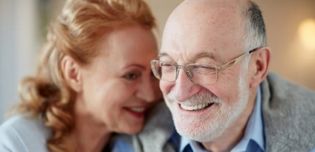 Man and woman with healthy smiles after gum disease treatment