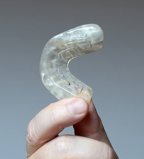 Hand holding a clear occlusal splint to treat T M J dysfunction