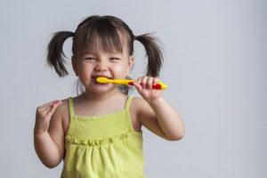 Little girl smiling while brushing her teeth