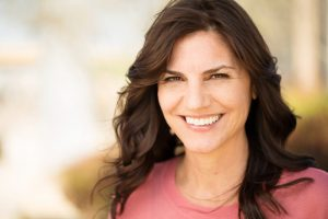 Woman smiling outside after seeing cosmetic dentist