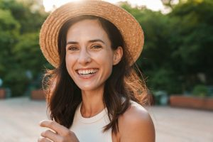 Woman who is protecting her smile while wearing a hat outside