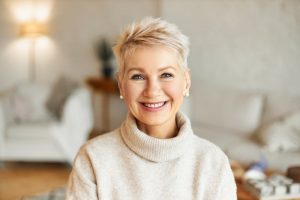 Woman in sweater thinking while smiling