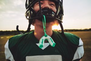 Boy playing football with mouthguard hanging from face mask